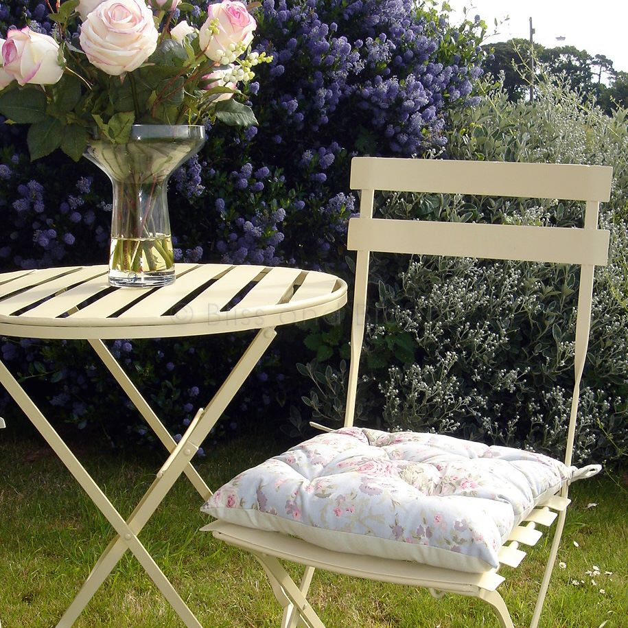 this metal table and 2 chairs set is a rich cream colour it has a